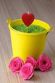 Yellow bucket with a green sea salt — Stock Photo