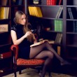 Girl in the home library — Stock Photo