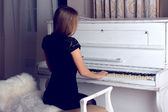 Girl in black dress playing on a white piano — Stock Photo