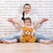 Mother, daughter and toy sitting against the wall - Stock Photo