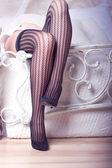 Beautiful female legs in fishnet stockings — Stock Photo