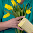 Hands of an adult woman with yellow tulips — Stock Photo