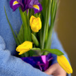 Woman hugging a bouquet of tulips and irises — Stock Photo