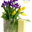 Tulips and  irises in a vase near gift — Stock Photo