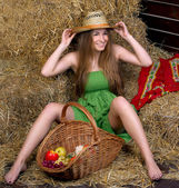 Girl in green dress a haystack — Stock Photo
