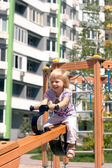Child on a swing high-rise buildings — Stock Photo