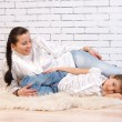Mother and daughter lying on a white fur — Stockfoto