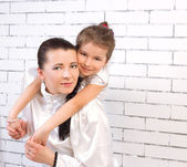 Daughter in a white dress hugging her mom — Stock Photo