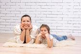 Mor och 5-åriga dotter liggande på golvet — Stockfoto