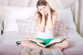 Girl on the bed reading a book — Stockfoto
