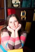 Chica en un suéter de rayas contra librería — Foto de Stock