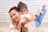 Daughter is on the back of a mother — Stock Photo