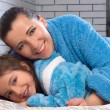 Female and girl in the same blue terry robes — Stock Photo