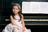 Cute 5 year old girl sitting by piano — Stock fotografie