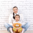 Stock Photo: Mother and daughter sitting, holding toy
