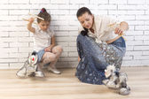 Mother and daughter playing with a toy dog — Stock Photo