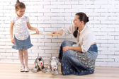 Mother and daughter playing with two toy dogs — Stock Photo