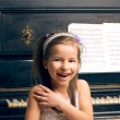 Girl in a beautiful dress near the piano happy — Stock Photo