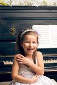 Girl in a beautiful dress near the piano happy — Stock Photo