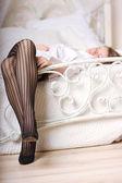 Attraktiva ben på vit säng — Stockfoto