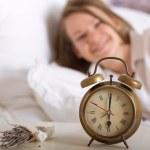 Alarm clock on table and woman sleeping — Stock Photo #24778969