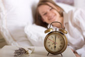 Alarm clock on table and woman sleeping — Stock Photo