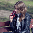 Girl on a park bench drinking - Stockfoto