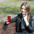 Girl on a park bench drinking - Stock Photo