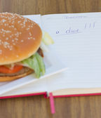 Burger and a diet diary — Stock Photo