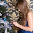 Girl dresses up Christmas tree — Stock Photo