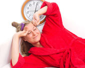 Sleepy woman with a clock — Stock Photo