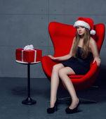 Noel şapka içinde oturan kadın portresi — Stok fotoğraf