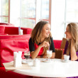Stock Photo: Two girls drinking coffee in cafeteria