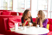 Two girls drinking coffee in a cafeteria — Stock Photo