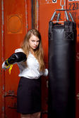 Angry businesswoman with boxing gloves — Stock Photo