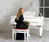 Young woman playing the white piano — Stock Photo