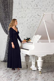 Beautiful young woman playing piano — Stock Photo