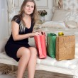 Pretty woman lying on a bed with shopping bags — Foto de Stock