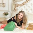Pretty woman lying on a bed with shopping bags — Stockfoto