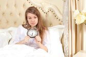 Young woman with alarmclock on the bed — Stock Photo