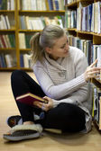 Girl sitting on floor in the old library — Stock fotografie