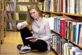 Girl sitting on floor in the old library — Stock Photo
