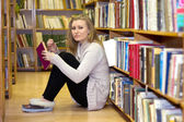 Girl sitting on floor in the old library — Foto Stock