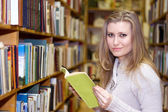 Student standing at bookshelf in old library — Foto Stock