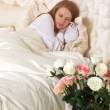 Beautiful sleeping woman in bed with roses — Stock Photo #43158741