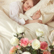 Beautiful sleeping woman in bed with roses — Stock Photo #43158847