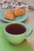 Cup of tea and croissants near blossoming branches — Stock Photo