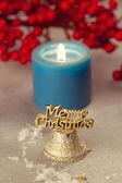 Christmas bells near burning candles — Stock Photo