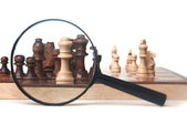 Chess pieces and magnifier — Stock Photo