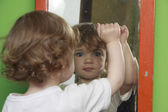 A child is looking through the dusty mirror. — Stock Photo